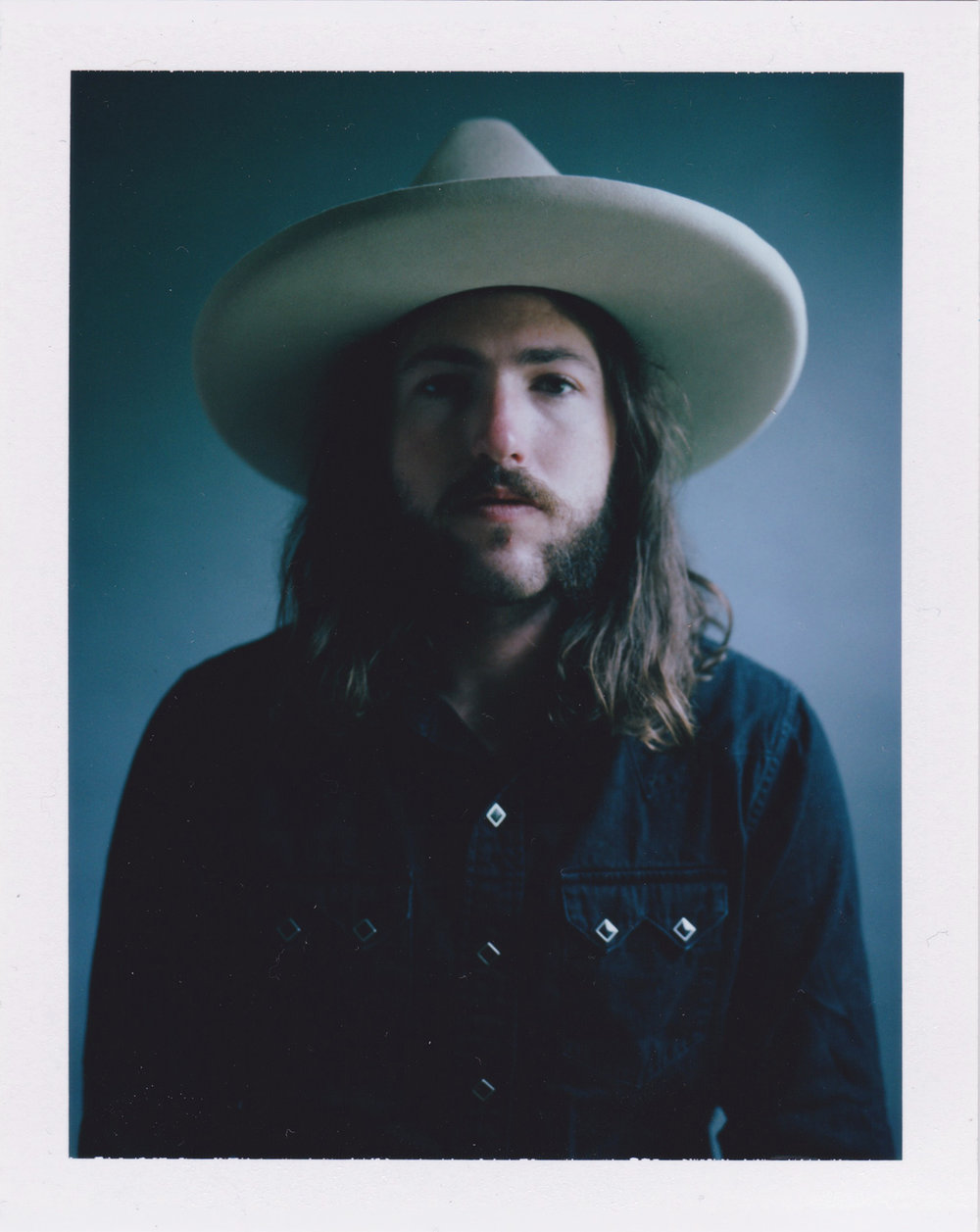"Danielle Atkins  • Nashville, TN  @daniellebatkins   I shot this image for some recent personal portrait work. It has been short on Fuji fp100c polaroid. The portrait is of my good friend Jordan ""Solly"" Levine. He is a drummer for a few country western music artists. He always has such great style and puts a lot of care into his look. I thought it suited the western prompt well."