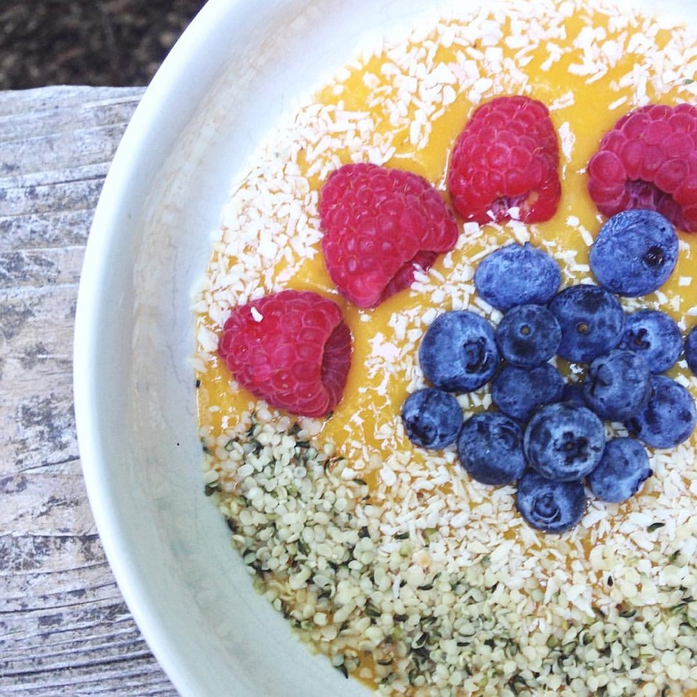 MANGO SMOOTHIE BOWL WITH SEEDS AND FRESH FRUITS.