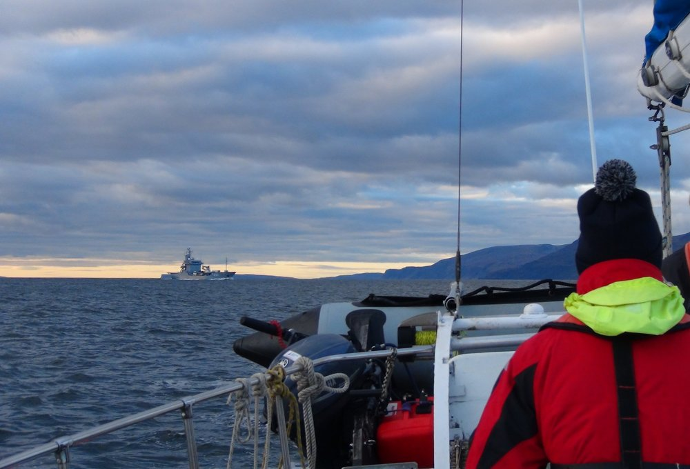 Volunteer look out towards a military vessel during a Joint Warrior Survey