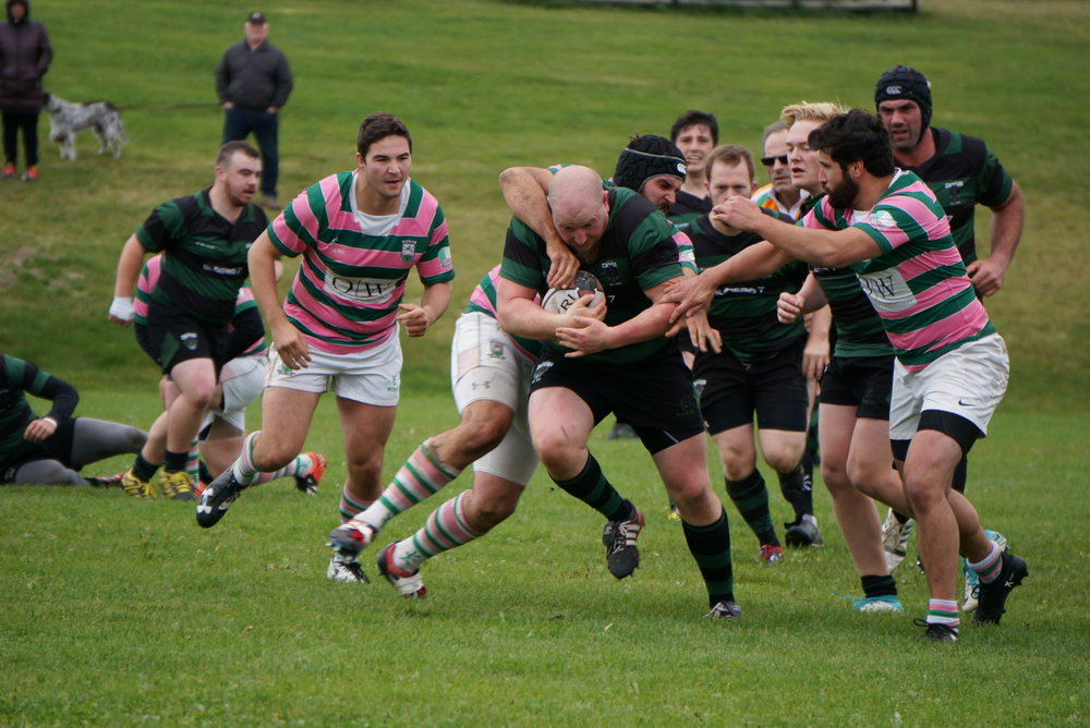 Dogs prop Steve 'Cutter' Cutcliffe carrying the ball, while Swilers lock Aaron Burrows tackles