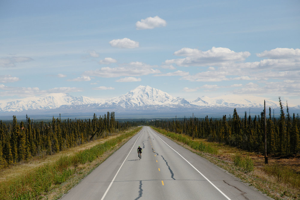 Man biking down empty road in Alaska