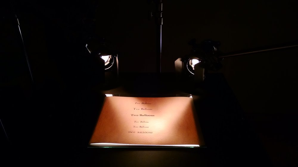 Testing the appearance of paper textures and pressed-in lettering under different kinds of computer-controlled lights.  Photograph by Vanessa Pridgen