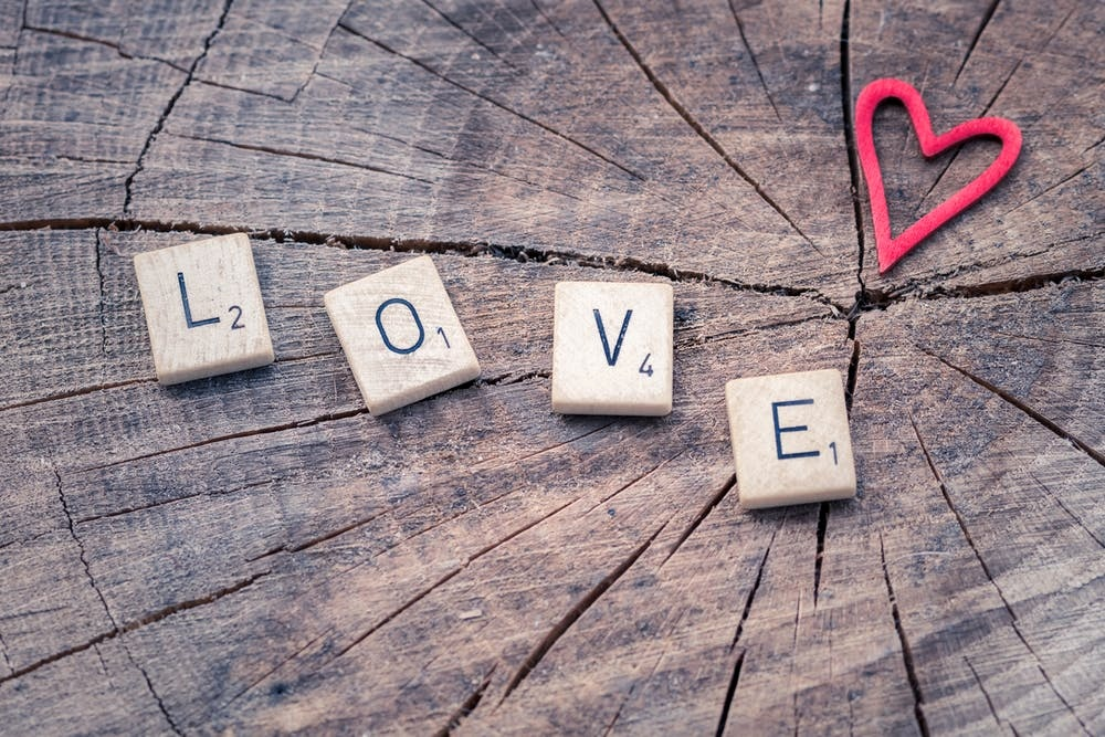 Four scrabble pieces spelling out the word LOVE, perfect image for a romance editing specialist offering romance novel editing services.