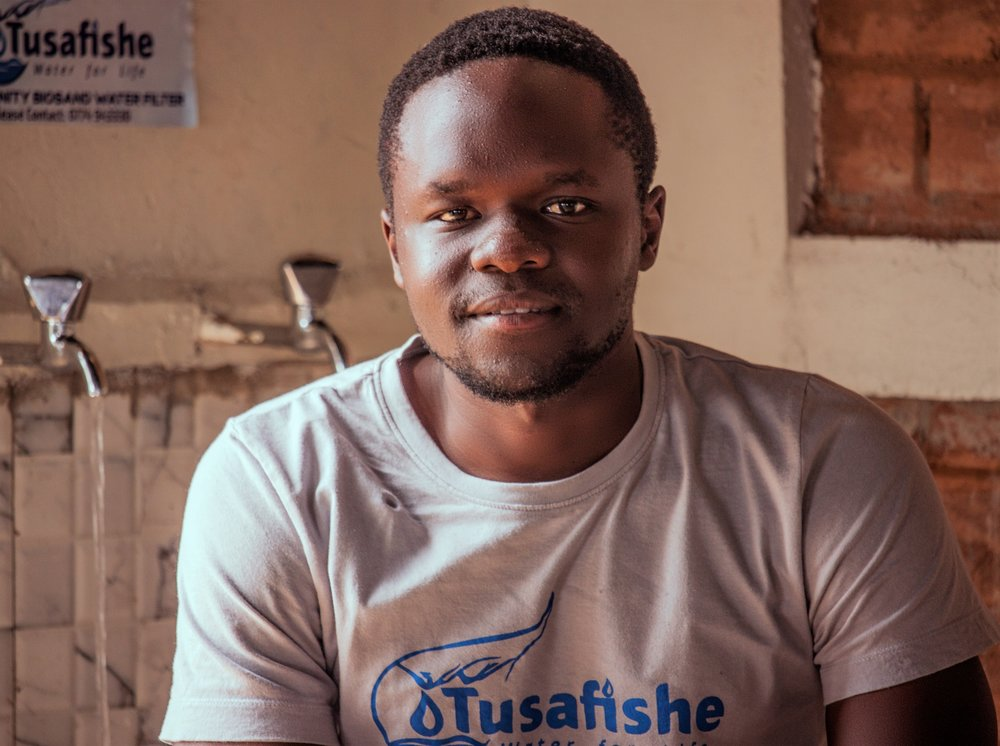 - Tonny Wamboga is the co-founder of Tusafishe and is completely passionate about water. He grew up in rural Uganda fetching water from a contaminated wells, having to walk 1.5kms to take the water home. He regularly fell sick and decided to do something about this problem, which many Ugandans face.As a scholar of the Social Innovation Academy (SINA), Tonny started the production of affordable water filters, using locally available resources. Tusafishe was born.Our planet has only 2.5% fresh waters and the wars of the future will probably be about access to drinking water. Already today, one-third of the African population has no access to safe drinking water and in Uganda it is almost half of the population. As a result of contaminated waters, 75% of all diseases in Uganda are waterborne.Tusafishe builds low-cost bio-sand water filter systems for safe and clean drinking water. With Tusafishe water is filtered through a natural process using granite sand. Bacteria and viruses are removed and safe water with nutritious minerals produced. The process emulates nature's way of filtering water through its soils and springs.Water filters are provided to rural public secondary schools in Uganda, who need them the most. One filter can supply up to 2000 students on a daily basis. Tusafishe also conducts trainings and sensitizations for communities to eradicate waterborne diseases and equip students with the skills to build and maintain filters using available resources, so as to replicate the solution in their homes.The goal is to eradicate waterborne diseases in Uganda by 2050.http://www.socialinnovationacademy.org/tusafishe/