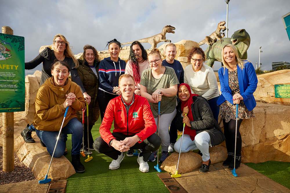Community representatives including Lisa Brown from Forever Manchester (bottom row, far left), Janet Davies from Salford Foundation – Eccles (back row, far left), Dean Lynch from Challenge 4 Change (back row, third from right) and Kelly Willison from Once Upon a Smile (front row, far right) join Pete Styles, director of golf, at Dino Falls and Trafford Golf Centre (front row, centre) for a celebration of Dino Falls first birthday.