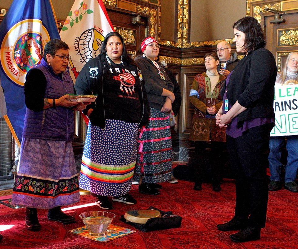 Ojibwe elder Sharon Day (far left) leads a traditional water ceremony.