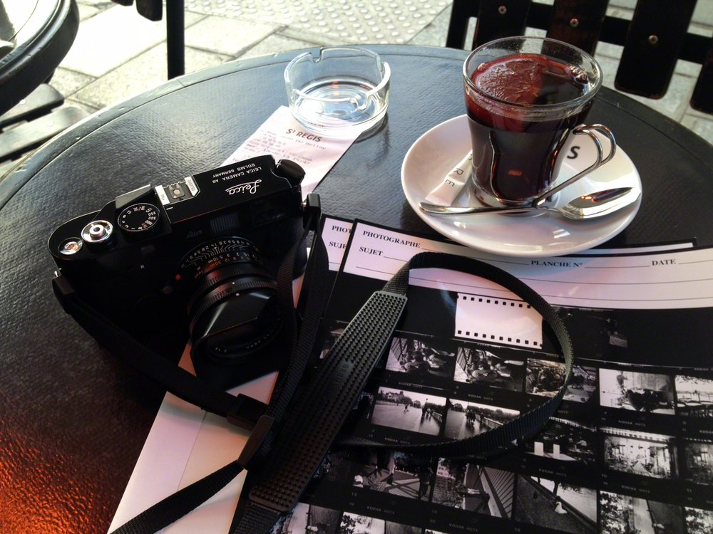 My Paris sojourns conclude with a glass of vin chaud (hot wine) while reviewing contact sheets of my film developed and printed by  L'Atelier Publimod .  A  recipe for vin chaud : 1 bottle red wine, 4 cinnamon sticks, 1-1/2-inch by ½-inch piece of orange zest (white pith removed), 4 tablespoons granulated sugar, 2 cardamon pods, 5 whole cloves, 1/3 cup Cognac. Mix all the ingredients together in a large saucepan. Bring the mixture to just under a simmer over the lowest heat setting on the stovetop. Do not allow the wine to boil. The mulled wine is hot enough when the sugar has dissolved and pulling and lifting a spoon from the wine brings up steam. If desired, strain the spices from the wine by pouring it through a fine-mesh sieve or a cheesecloth-lined collander. Add 1-2 teaspoons of Cognac to a mug and ladle the mulled wine over it.