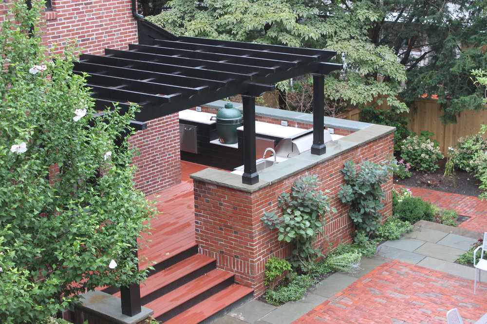 Outdoor kitchen, brick exterior, landscaping and pergola.