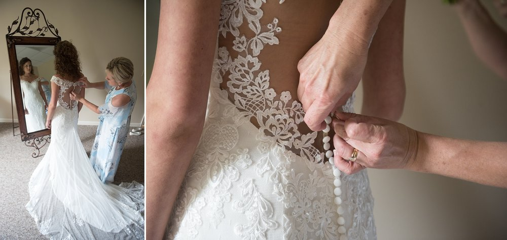 close up of bride being buttoned into her lace wedding dress by her mother