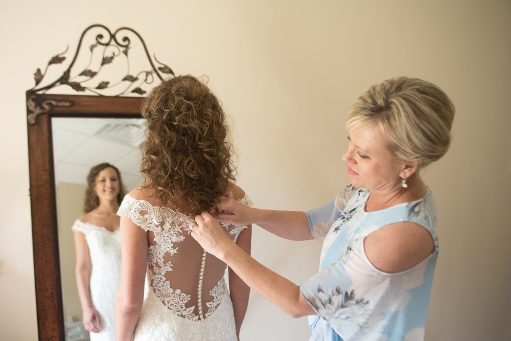 Bride standing in front of decorative mirror while her mother buttons her lace wedding dress