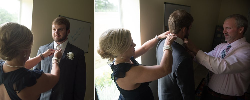 Mother and Father of the groom adjust the groom's tuxedo