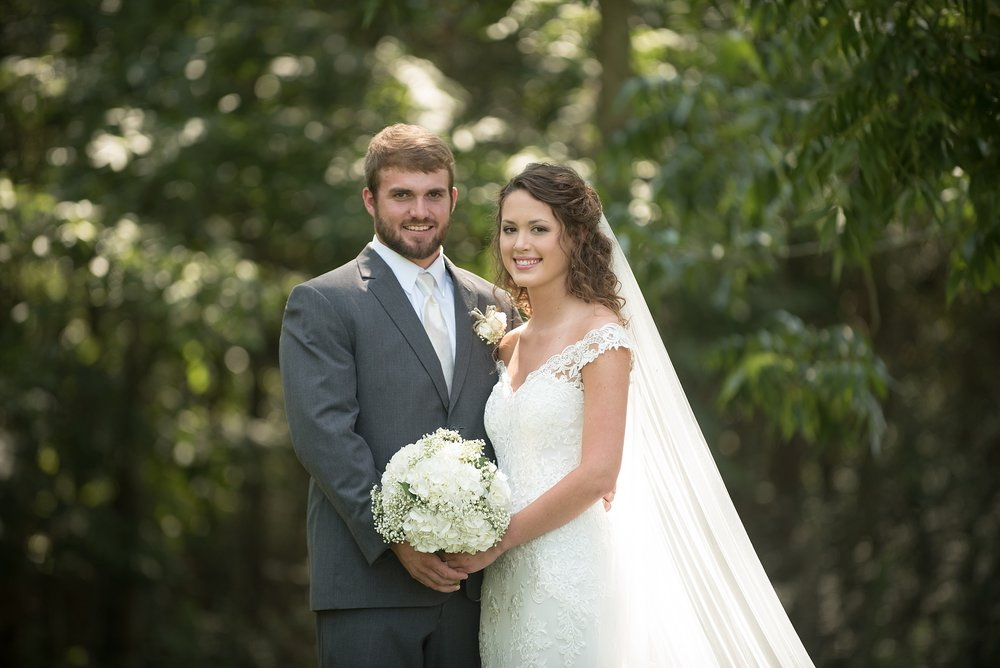 handsome groom in his tuxedo hold onto bridal bouquet with bride in lace wedding dress