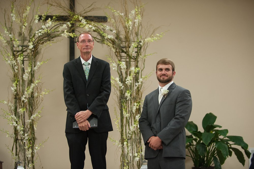 groom and pastor wait at the altar in the church for the bride