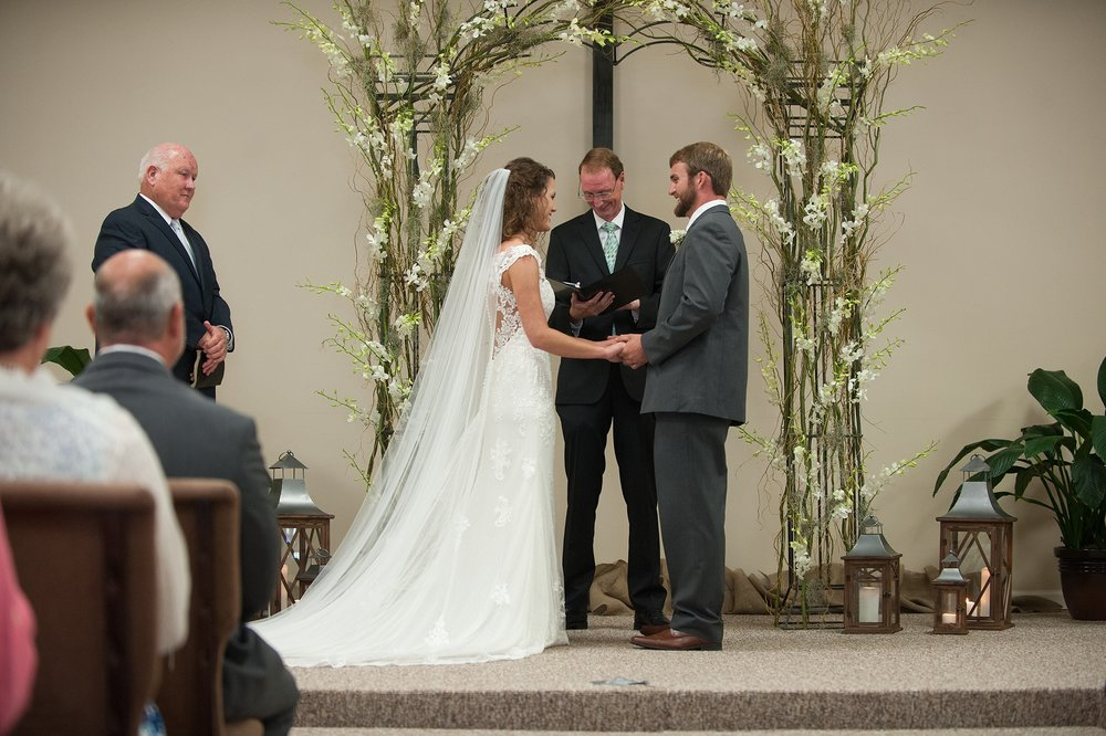 beautiful floral and twig arch framing the bride and groom with the pastor during the wedding ceremony