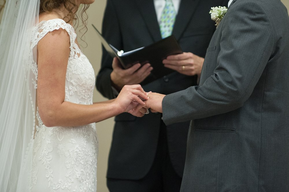 closeup of the bride placing the wedding ring on the groom's finger