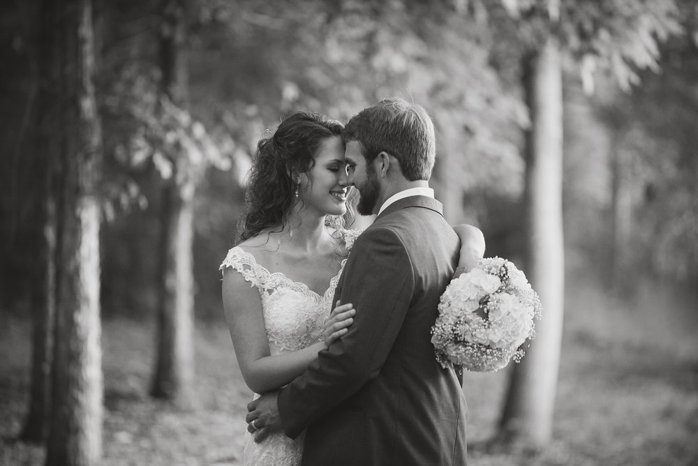 black and white picture of the wedding couple embracing in a dreamy wooded setting