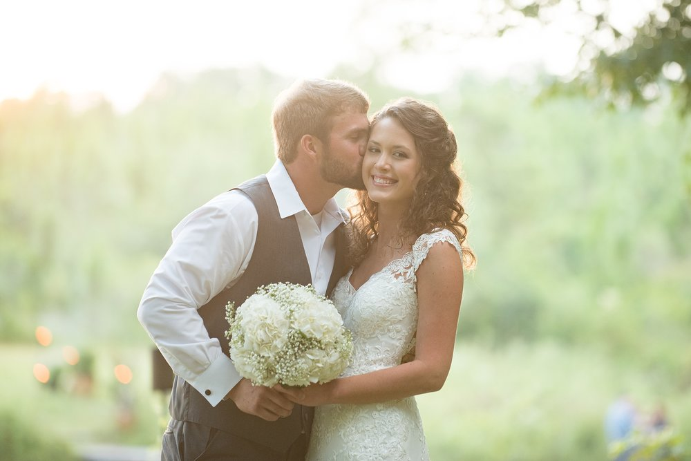 bride laughs as groom whispers in her ear while they hold the bridal bouquet