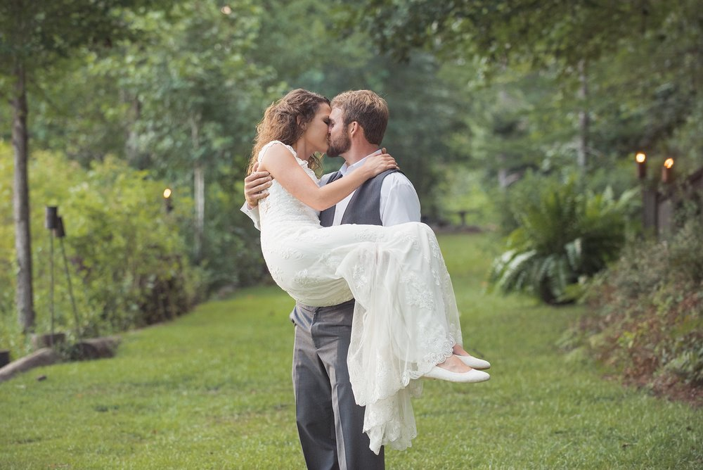 groom carries bride in his arms, giving her a kiss