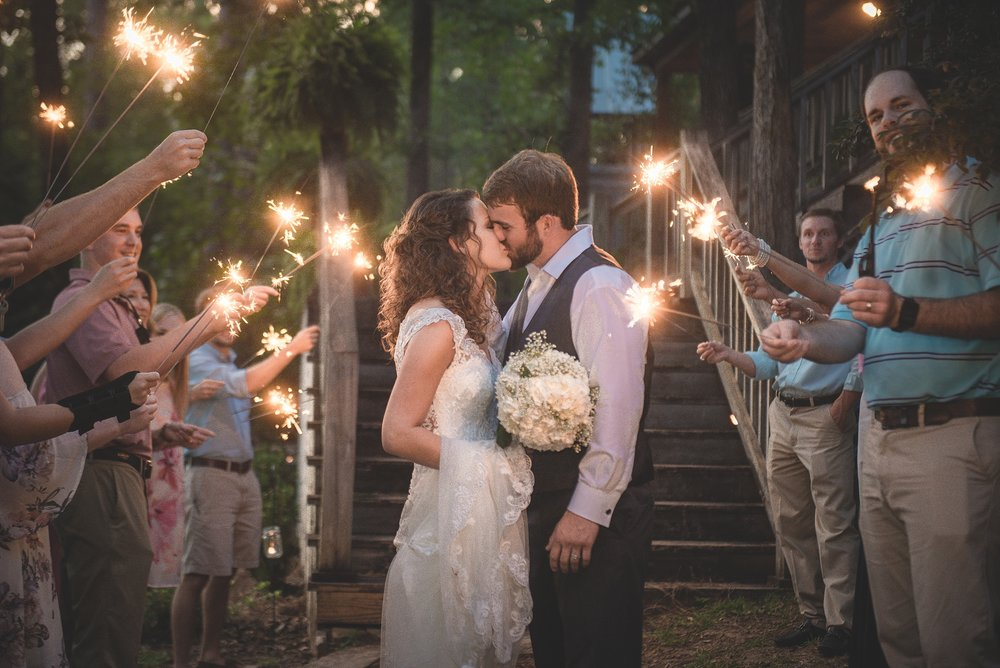 Sparkler exit as couple kiss in a tunnel of people and twinkles