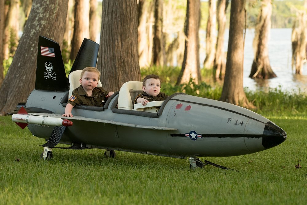 infant brothers sit in toy fighter jet that their dad built