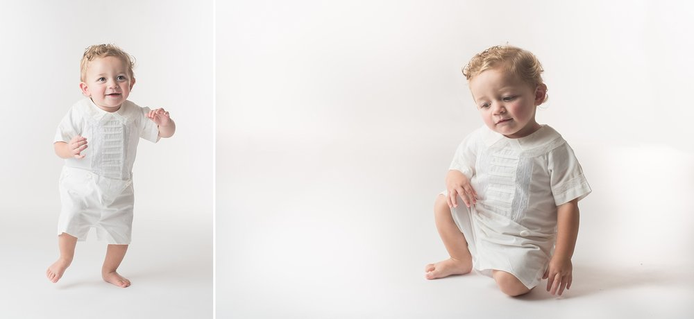 One year old boy in white heirloom outfit takes wobbly steps on a bright white background