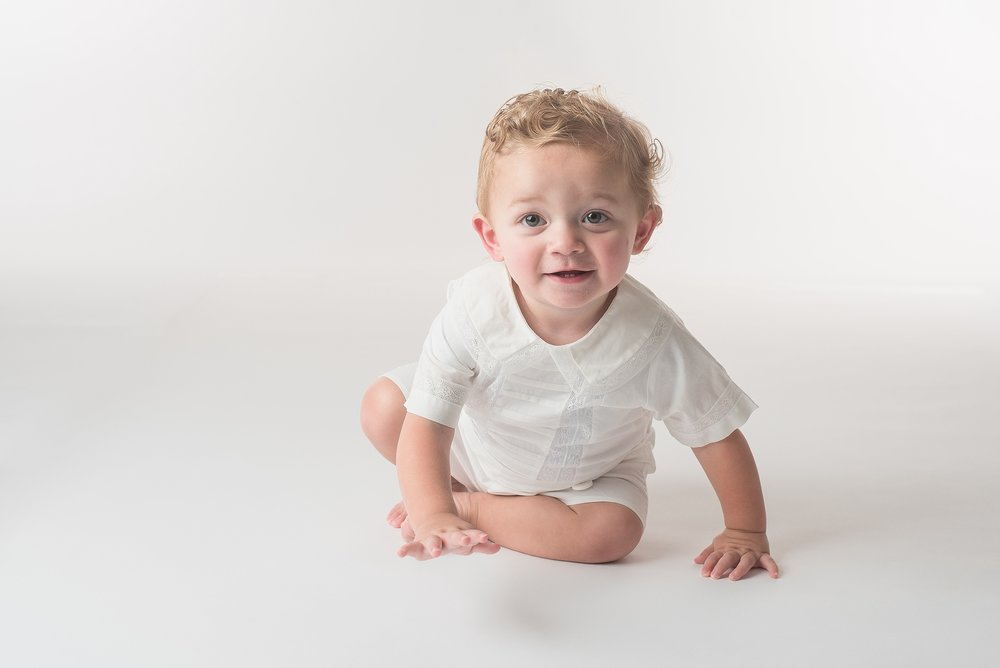 One year old boy in white heirloom outfit crawls toward the camera