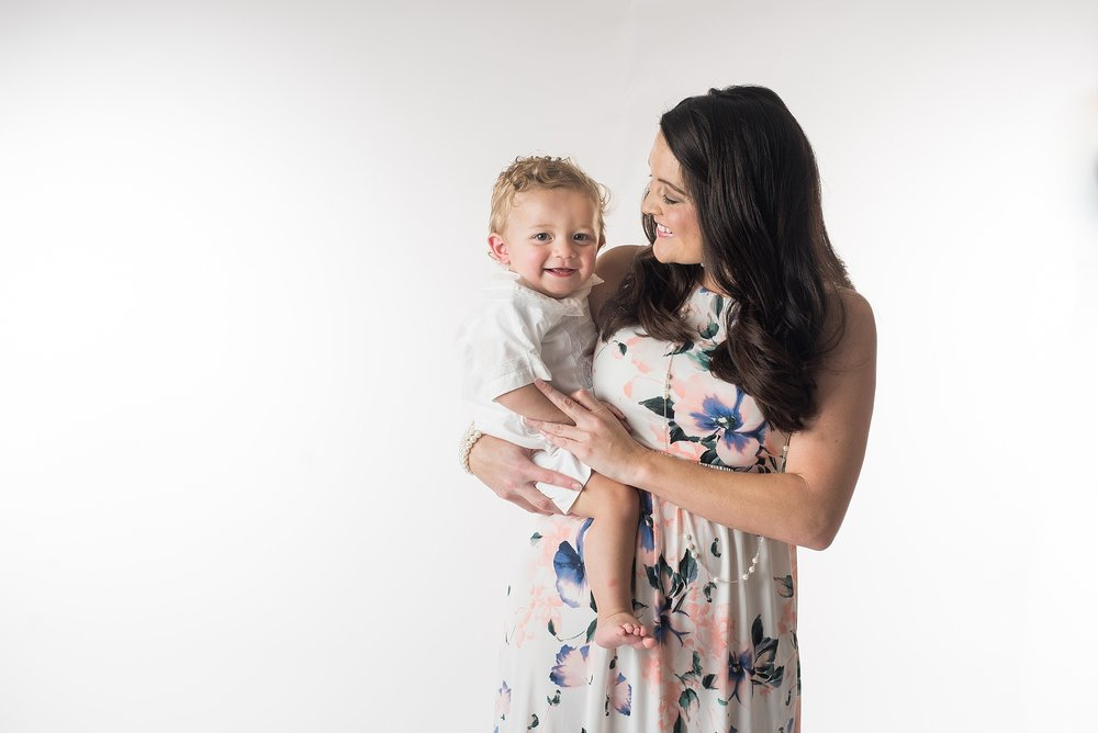 mother holds one year old boy on her hip on a white background