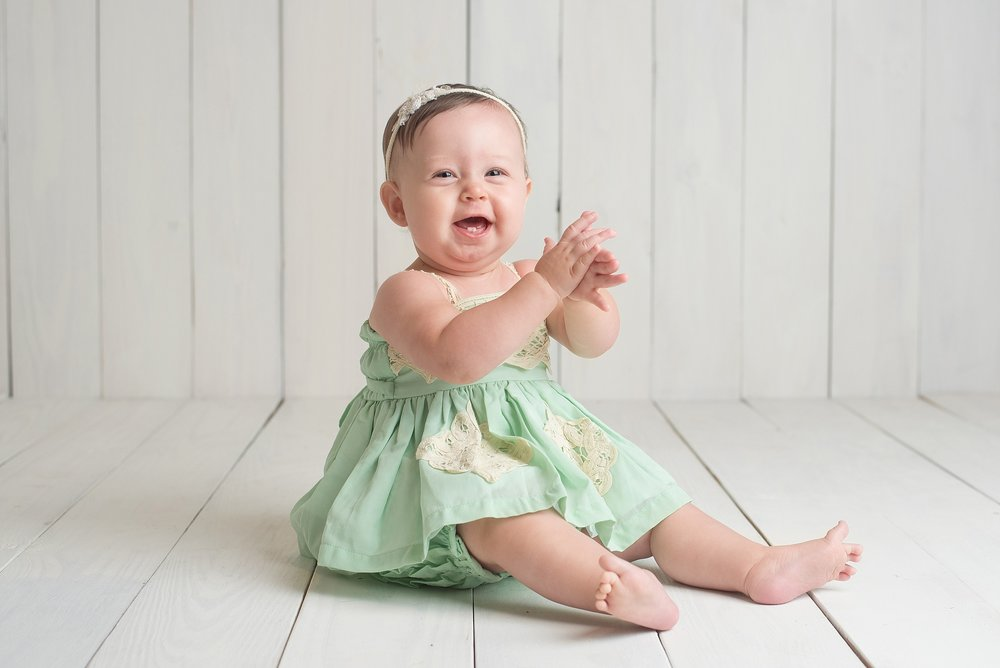 9 month old baby girl in a mine dress on a wooden background