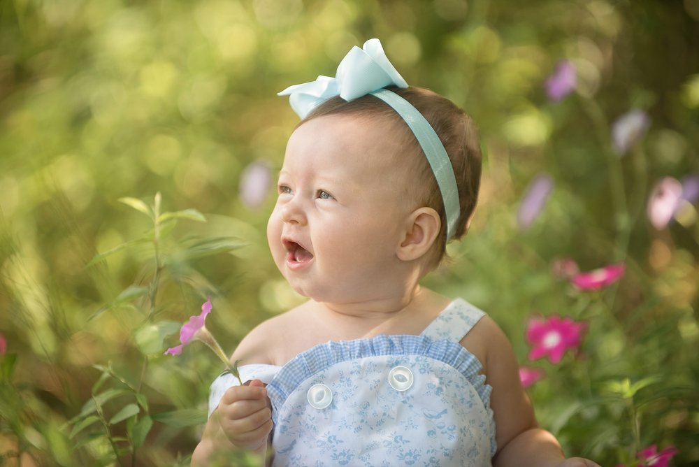 baby girl outside in the flowers