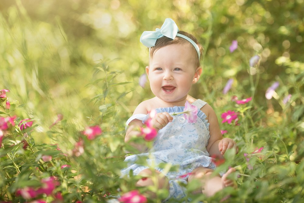 baby girl holds flower outdoors