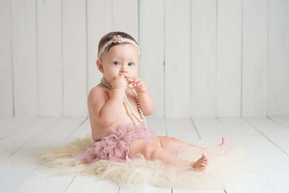 baby girl in pink tutu chews on a pearl necklace