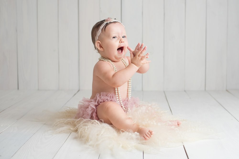9 month old baby girl in pink tutu claps and laughs
