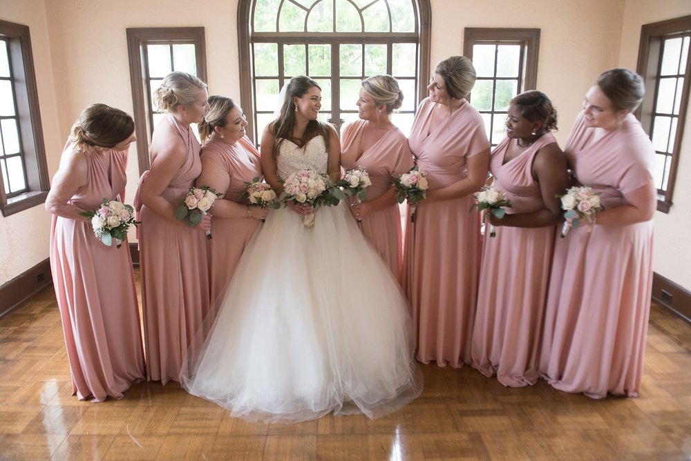 Bridesmaids in pink convertible maxi dresses share a moment with the bride.