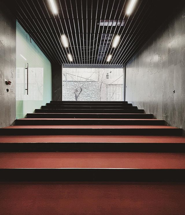 Fit-out in-progress; a multi-purpose hall with a full-width fixed window was created for office events. The stepped floor is an exact offset of the parking ramp below - Jordan Office Building - Photo by PauseGroup #hall #office #amenities #architecture #interiordesign #steps #stone #multipurpose #carpet #interior #window #street #event #tehran #iran