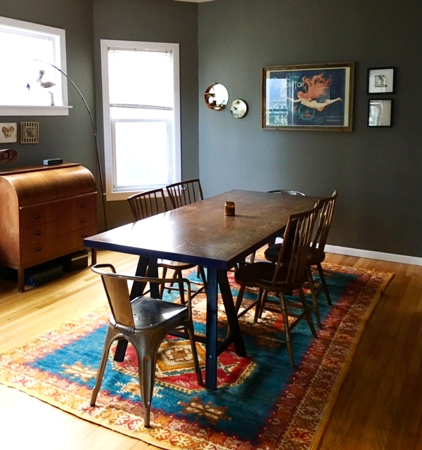 Check out that good orange in the rug, the print, and the rolltop desk.  Table is a door from Restore (Habitat for Humanity resale) and  two table horses from Ikea , flea market rug
