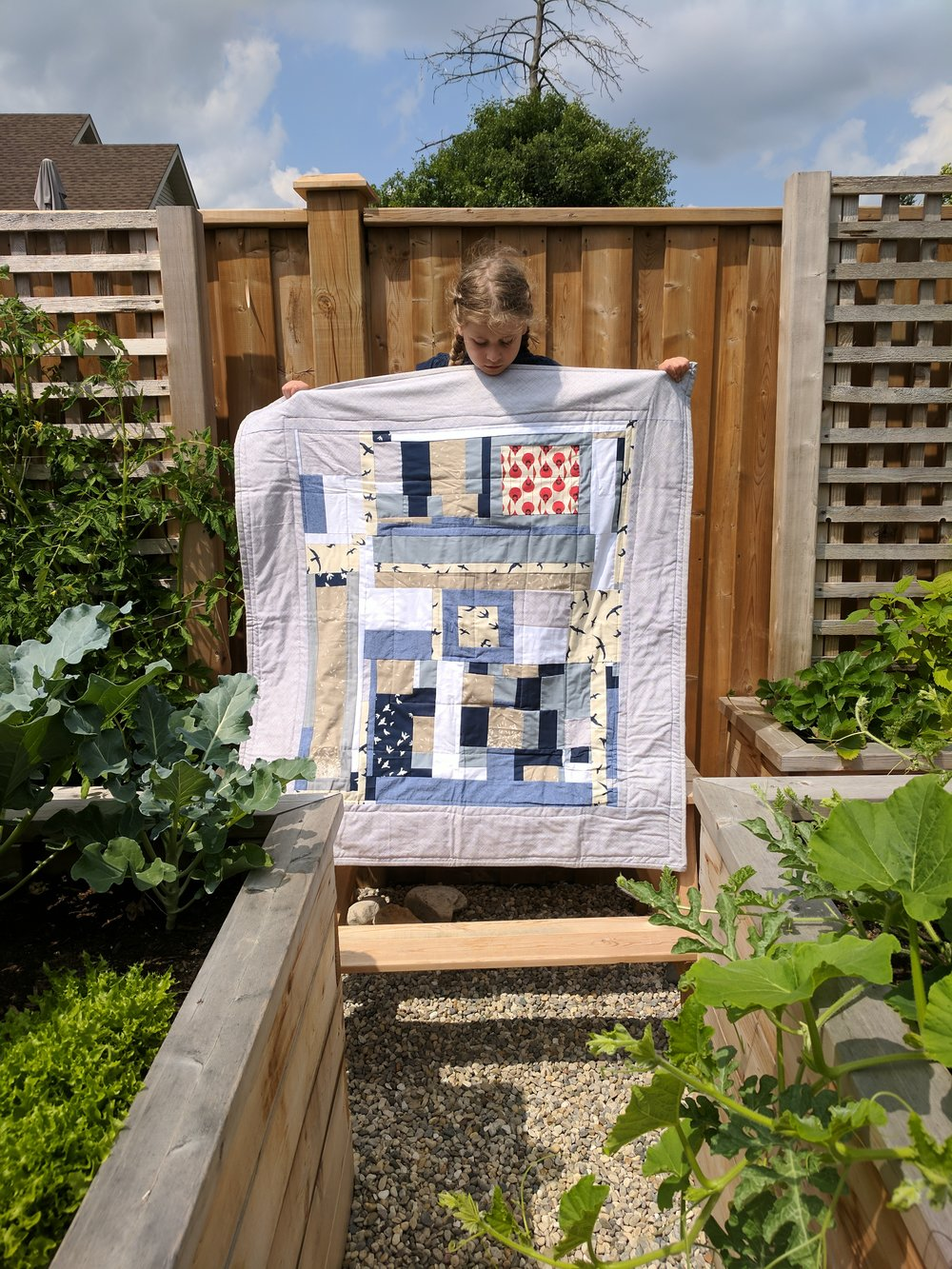 Zoe holds up a small quilt I just finished for our good friends' brand new baby boy.