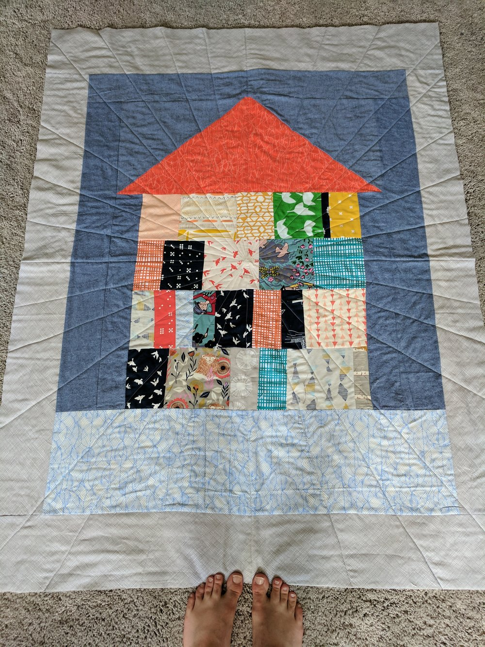 Zoe and I collaborated on this baby quilt for my nephew Cooper. Zoe found the orange triangle in a scrap bucket and thought it looked like a roof. She laid it out on the floor of the sewing room while I was working on something else, and started to make a rectangle beneath it out of other scraps. She found the big blue rectangle and thought it looked like water. She called it The Lake House Quilt.
