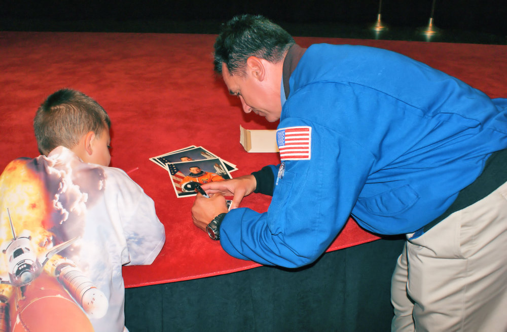 DSC05570 Anthony LaPan watching   astronaut William Oefelein sign a picture for him.jpg