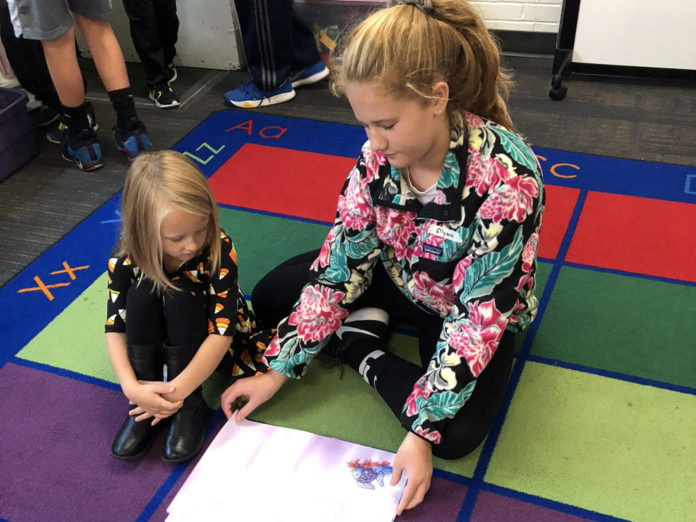 Ellyana Teliczan helps her Grandville kindergarten partner read through the book she chose