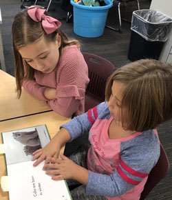 Ally (left) reads with her penpal from Central Elementary in Grandville