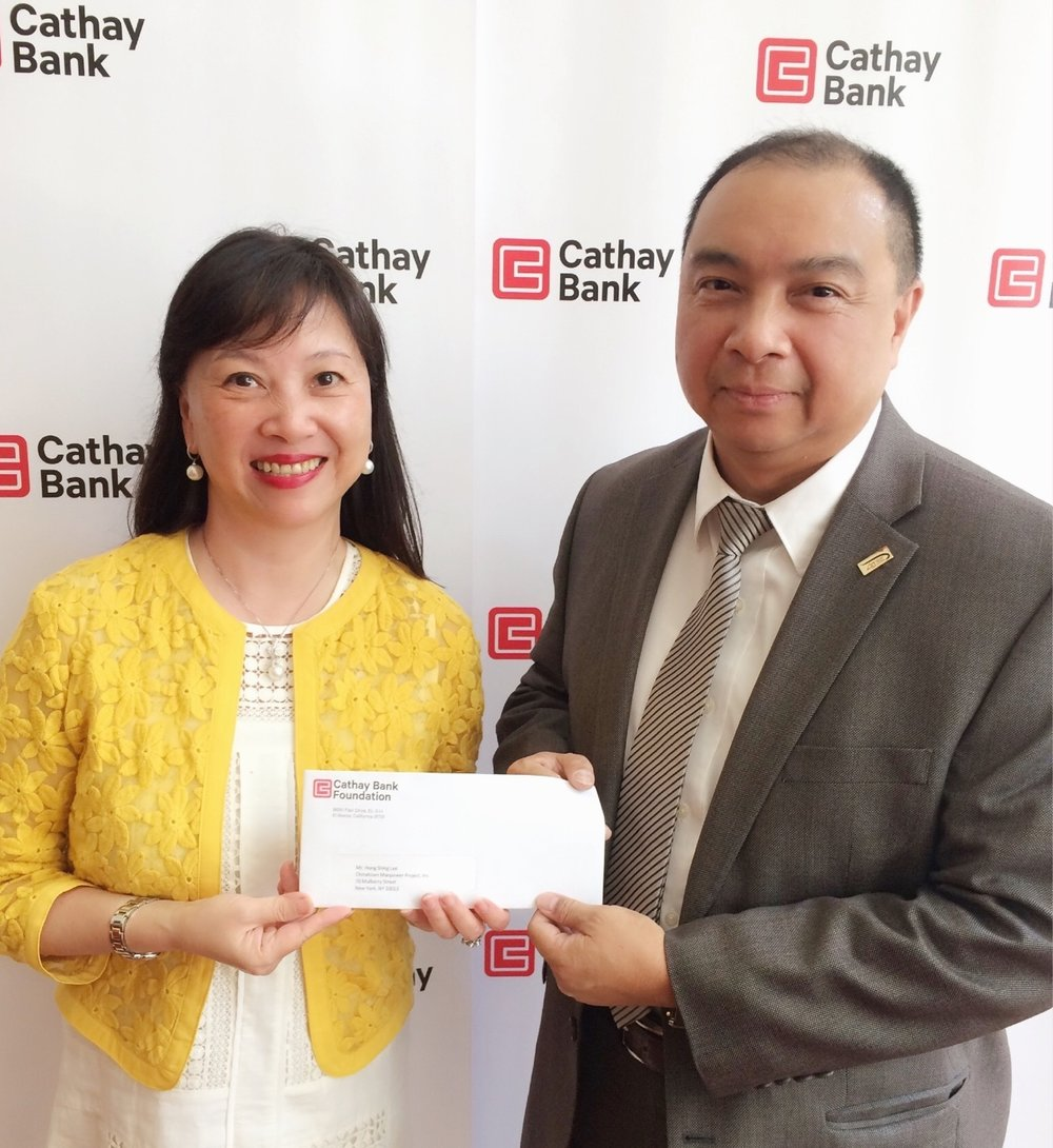 Cathay Bank Senior Vice President  Ms. Elizabeth Lee  (left) is handing over the donation check to CMP Executive Director  Mr. Hong Shing Lee  (right).