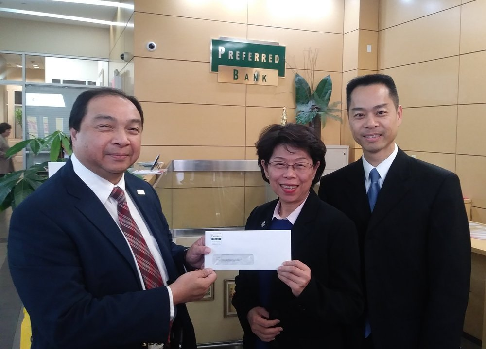 Preferred Bank Executive Vice President  Ms. Kathy Yen  (center) and Senior Vice President  Mr. MK Chow  (right) handing over the donation check to CMP Executive Director  Mr. Hong Shing Lee  (left)