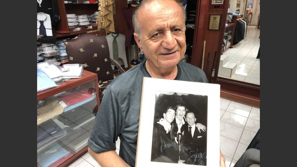 Custom clothier George Yaghi with a prized photo of Dean Martin, Jerry Lewis and Frank Sinatra. Marilyn Monroe formerly lived in a home that Yaghi turned into his clothier shop on East Desert Inn that catered to celebrity clientele.