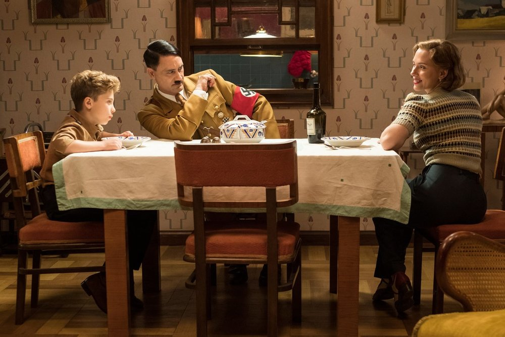 From left: Roman Griffin Davis as Jojo, writer/director Taika Waititi as his imaginary friend Adolf and Scarlett Johansson as his mother Rosie in the upcoming World War II satire  Jojo Rabbit .