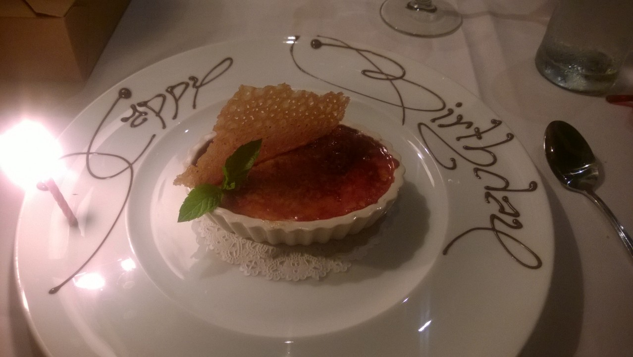 "Creme Brulee at the Ringside restaurant. ""Happy Birthday"" is written on the plate."