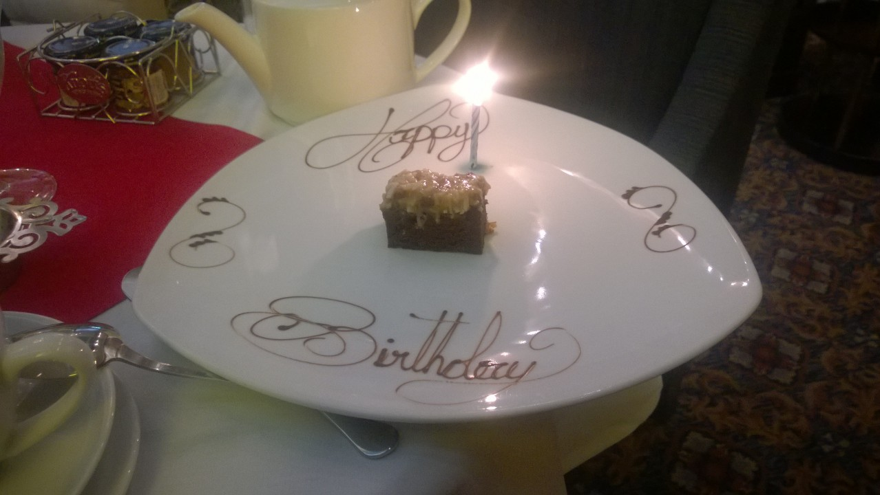 "Desesrt at the Heathman at afternoon tea. ""Happy Birthday"" is written on the plate."