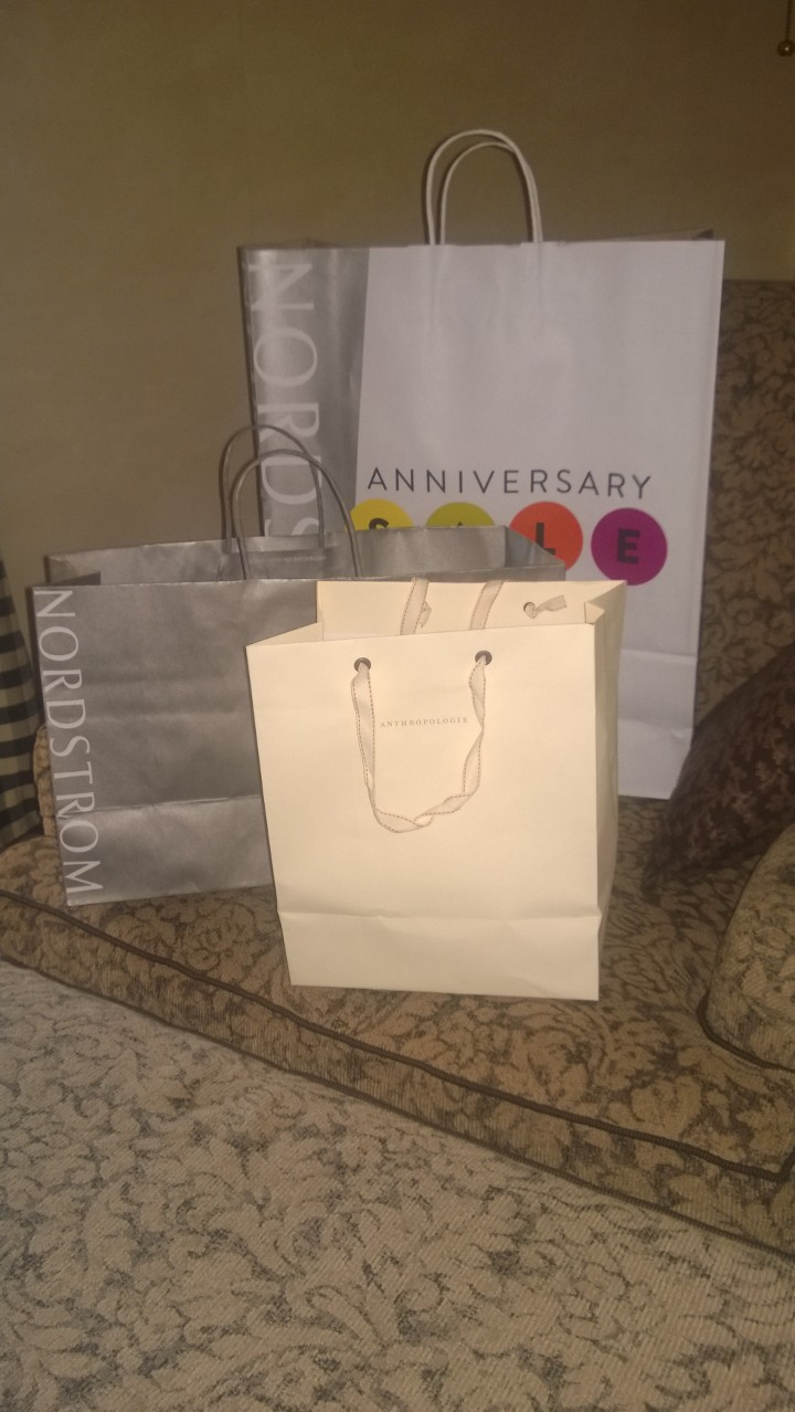 Three shopping bags, two from Nordstrom, one from Anthropologie.