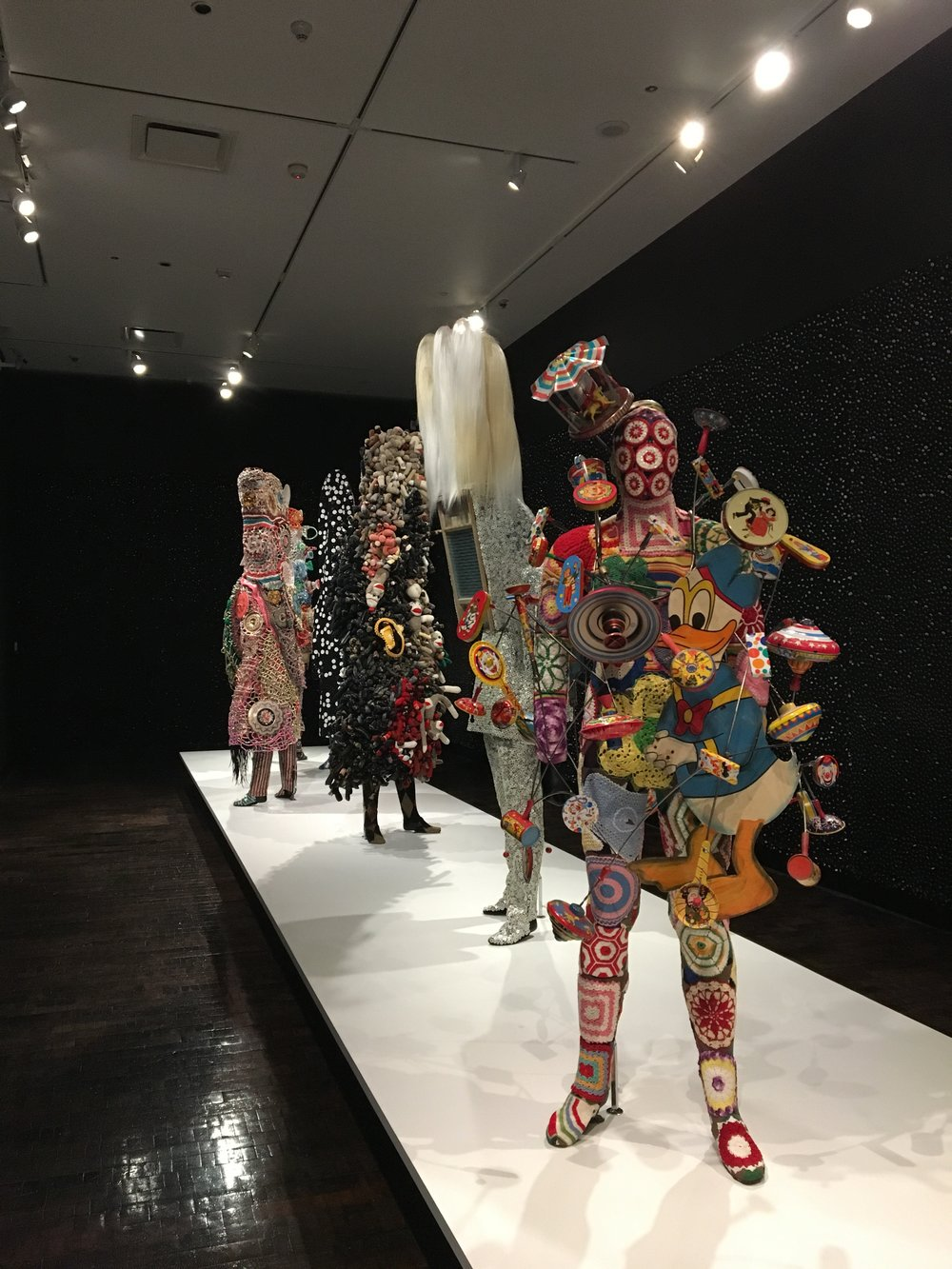 (Front sculpture) Nick Cave,  Soundsuit , 2016, mixed media, including vintage toys, wire, metal, and mannequin. Courtesy of the Lewis Family.