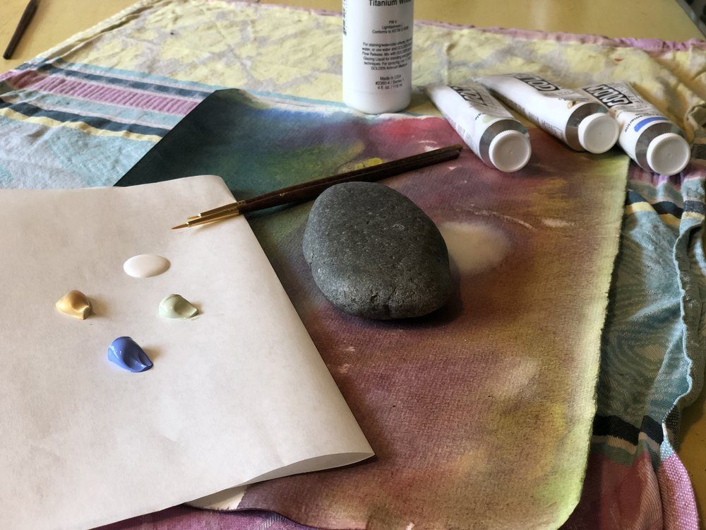 2. Gather your materials: stones, craft paints, matte varnish, paint brushes and paint pallet. We chose white, light blue, light green and a gorgeous gold (a precious element found deep within mountains!) for our paints and love the use of wax paper for our palette. While you work, listen for birdsong outside your window, or the sound of the wind in the trees. See this as a sacred presence around you while you create this item for your seasonal altar.