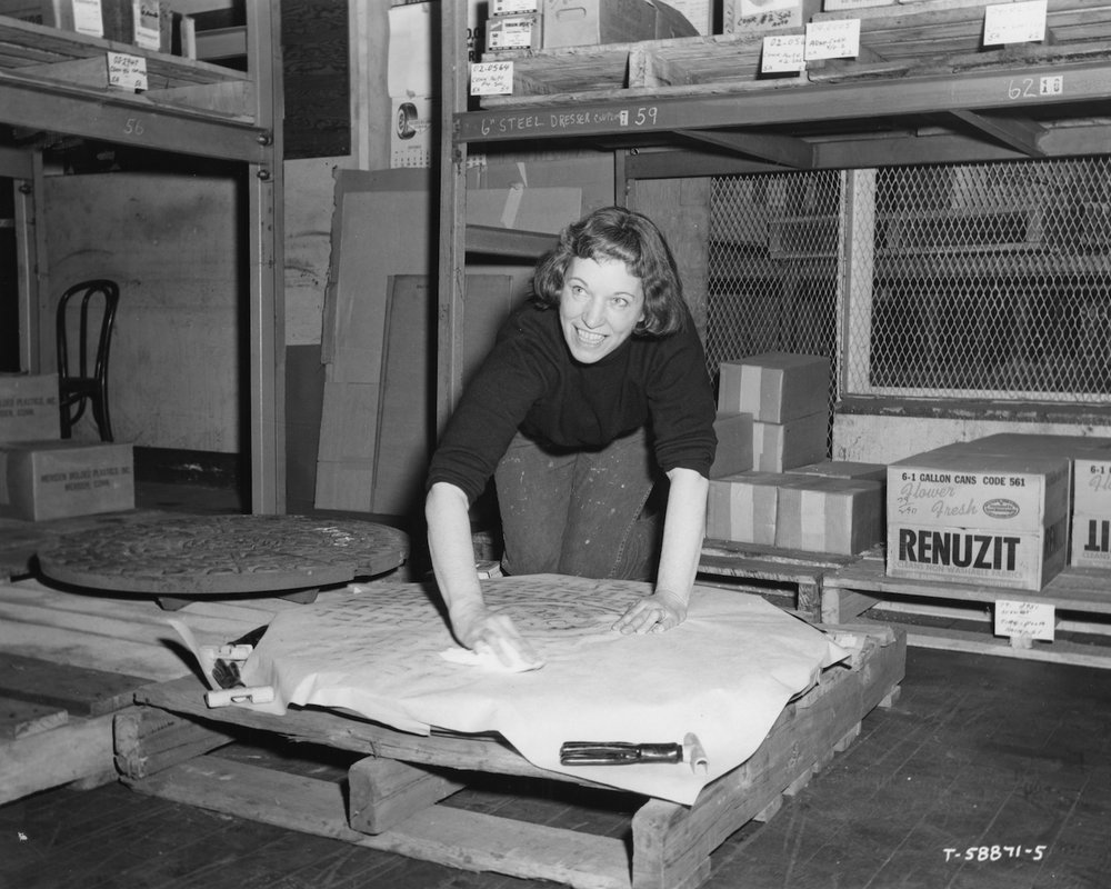 Dorothy Grebenak making a rubbing of a manhole cover, circa 1964